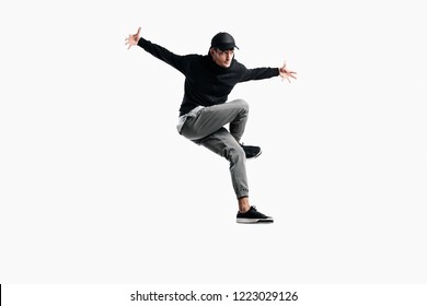 Stylish young man wearing a black sweatshirt, gray pants and a cap is dancing hip-poh