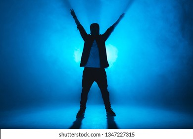 Stylish young man wearing trendy streetwear is dancing contemporary street dance on a blue studio background