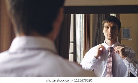 Stylish young man in white shirt stands by the mirror tying a tie