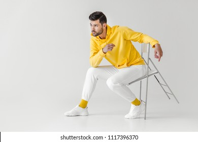 stylish young man in yellow hoodie sitting on chair on white
