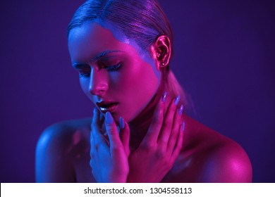Stylish young model with lowered eyes with hands near face. Her shoulders are open Background photos purple. Close Up Shoot.