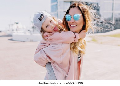 Stylish young mom holding her pretty little daughter. They are have fun outdoor with happy faces. Dressed in pink jackets, bright sunglasses and cap. Sunny summer day.