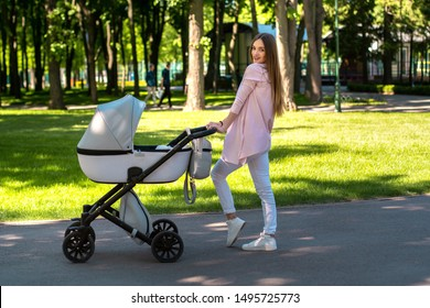 Stylish young mom walks with stroller in the park