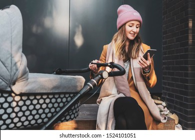 Stylish young mother in pretty clothes sitting on bench outdoors. Woman wearing coat, scarf and cap. Female parent walking with baby stroller and using smartphone for online communcation via messenger