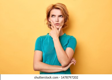 stylish young puzzled woman touching her chin and looking sideways with doubtful and sceptical expression. close up portrait