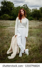 stylish young red haired woman posing outdoors
