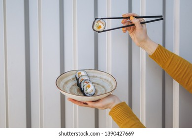 A stylish young smiling girl poses for a photo and holding in her hand a plate of rolls and chopsticks in the other hand. Appetizing advertising photography for restaurant, sushi bar, delivery