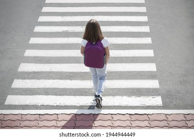 Stylish young teen girl walking with backpack. Active child. Kid runs across the crosswalk. Way forward. Direction to success. Positive thinking. Symbol of overcome obstacles and challenge. Top view