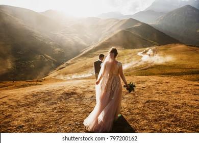 Stylish young wedding couple has fun posing in beautiful Georgian mountains
