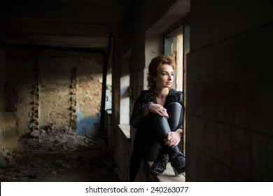 Stylish young woman in an abandoned building