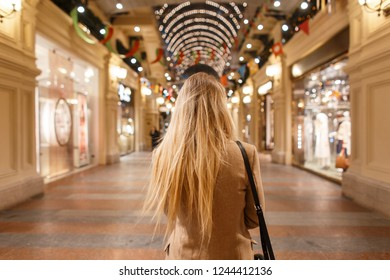 Stylish young woman blonde with long hair in a stylish beige vintage coat with a fashion black bag walks shopping and enjoys a festive atmosphere. Fashionable elegant girl.