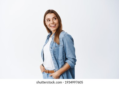 Stylish young woman in casual clothes, standing in profile and turn head right at copy space with advertisement, reading promo deal, standing against white background