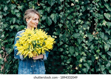Stylish young woman in denim clothes with a bouquet of mimosa against the wall with bright foliage.