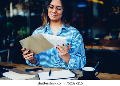 Stylish young woman entrepreneur in eyeglasses packing letter in envelope with mock up area sitting at coffee table with cup of cappuccino.Cropped image of beautiful female working with documents