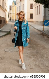 Stylish young woman with a handbag in jeans clothes in trendy shoes on the street