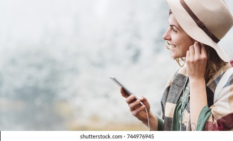 Stylish young woman with hat listening music using mobile phone in first snow. Traveling among stunning winter landscape. Vacations in mountain wilderness. Wanderlust and boho style