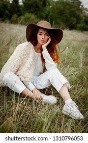 stylish young woman in hat posing outdoors