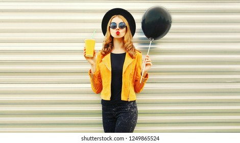 Stylish young woman having fun blowing red lips sends air kiss holding black air balloon, cup of fruit juice in round hat, yellow jacket on metal wall background