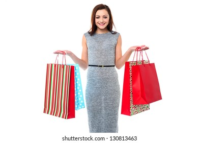 Stylish young woman holding vibrant shopping bags.