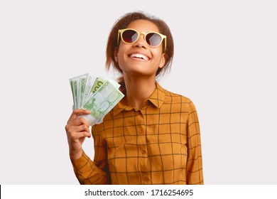 Stylish young woman holds large amount of cash in her hand. Concept of financial success, wealth and prosperity. Portrait of cheerful woman in sunglasses in a checkered shirt isolated on white wall.