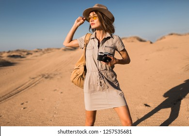 stylish young woman in khaki dress walking in desert, traveling in Africa on safari, wearing hat and backpack, taking photo on vintage camera, exploring nature, hot summer day, sunny weather