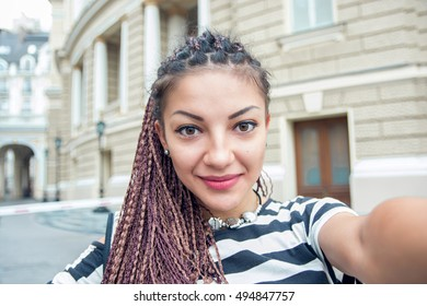 Stylish young woman making selfie at the street