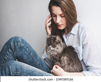 Stylish, young woman with mobile phone gently holding a kitten on a white background. People, care, pets, technologies