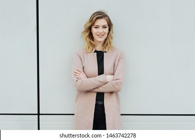 Stylish young woman posing against a white wall with black divider lines looking at the camera with a quiet smile and folded arms