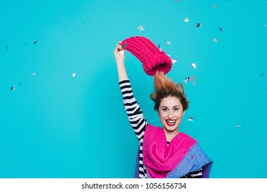 Stylish young woman removes a knitted pink hat from her head in the studio on a blue background. Winter goodbye. Spring comes. Lifestyle, youth, fun