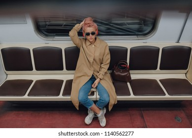 Stylish young woman sitting at empty subway train. New social distance