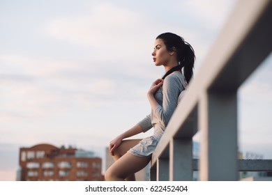 Stylish young woman sitting on roof and relaxation, evening city background
