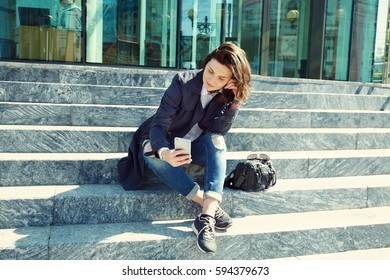 stylish young woman with smartphone sitting on the steps