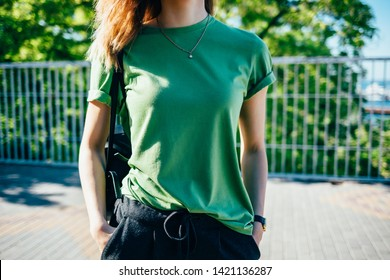 Stylish young woman standing at sunny green street. Female wearing t-shirt holding her hands in pockets. Close-up details of women's basic summer clothing.