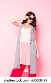 Stylish young woman in sunglasses posing in studio on the pink background,