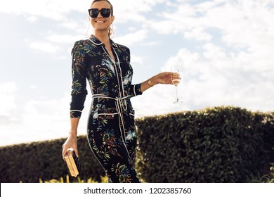 Stylish young woman walking with glass of wine. Wealthy female with wine walking outdoors.
