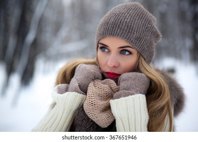 stylishly dressed beautiful young girl in a fur vest walks in winter park