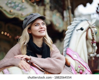 Stylishly dressed blonde with blue eyes in a black cap and pink sweater rides a French carousel. Parisian woman on a traditional French carousel.