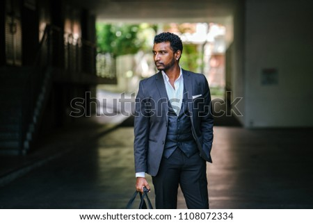 979244996e85 A stylishly dressed Indian Asian man stands in the street in the daytime. He  is