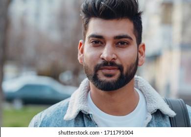 Stylishly dressed Indian bearded man walks down the street.