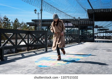 stylishly dressed middle-aged woman playing hopscotch, having fun as a child, jumping and smiling in the fresh air.