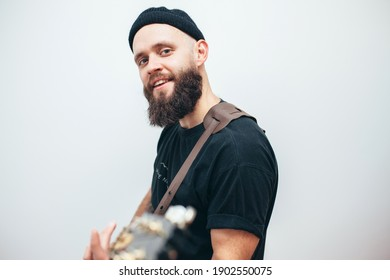 Stylishly dressed rock musician with a beard plays electric guitar