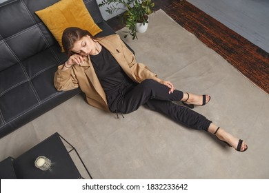 Stylishly dressed young caucasian woman in beige blazer and black pants sitting on the floor at sofa. Interior fashion portrait