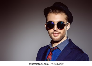 Stylishly dressed young man smiling at camera. Fashion studio shot.