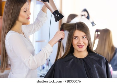Stylist blow drying hair of a client at the beauty salon.