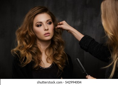 Stylist corrects hair of girl