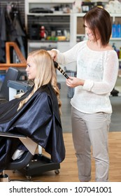 Stylist curling hair of a young blond customer