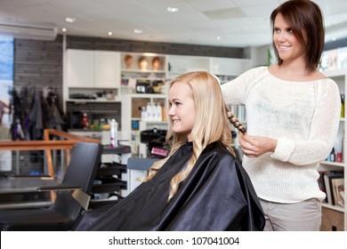 Stylist curling womans hair in beauty salon .