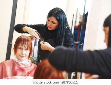 Stylist cutting hair of a female client at the beauty salon