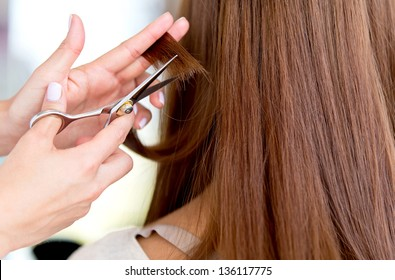 Stylist cutting split ends on her client at the salon