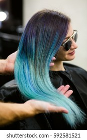 Stylist demonstrates his work with Beautiful girl. Barber haircut dyed hair color blue.